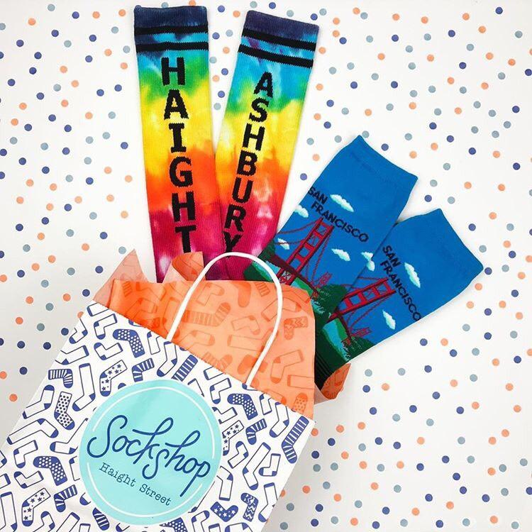 Brightly colored socks coming out of patterned gift bag with tissue paper